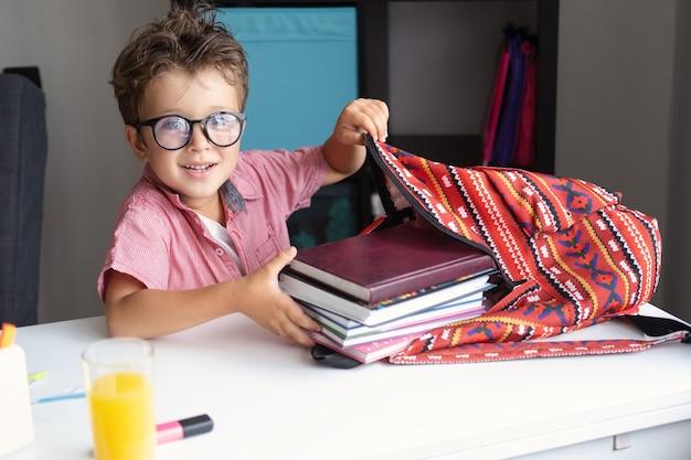Ładny mały chłopiec w okularach, pakowanie plecaka, przygotowanie do szkoły siedząc przy biurku i odrabianiu lekcji w domu. powrót do koncepcji szkoły.