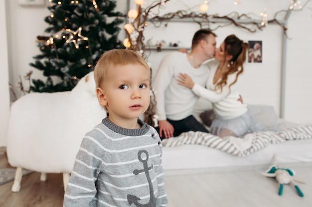 Ładny mały chłopiec w szarym swetrze stojący w studio i odwracając wzrok, podczas gdy młodzi rodzice w miłości przytulanie i całowanie za