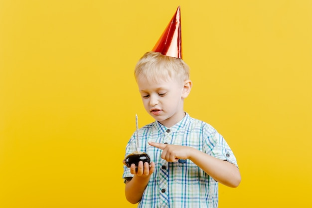 Ładny mały chłopiec w urodziny kapelusz i tort na żółto