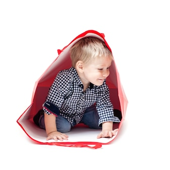 Ładny mały chłopiec wewnątrz czerwonego pakietu. koncepcja własnego domu z zabawkami
