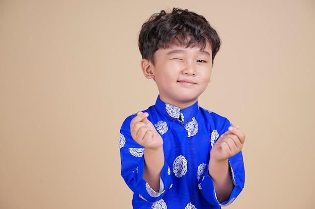 Ładny mały chłopiec wietnamski w sukience dai uśmiechnięty.