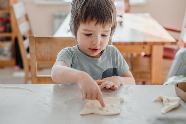 Ładny mały chłopiec wyrabiania ciasta na ciasteczka w kuchni
