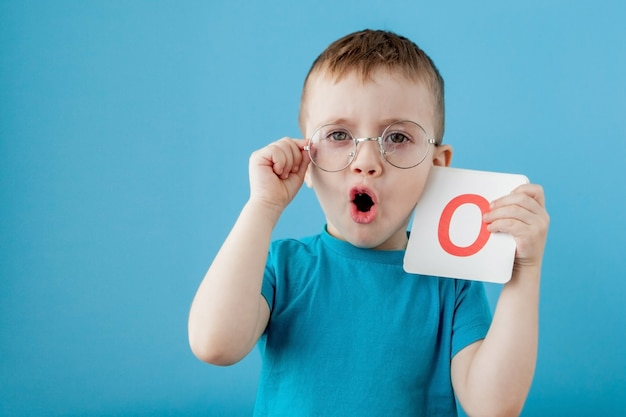 Ładny mały chłopiec z listem. dziecko uczy się listów. alfabet
