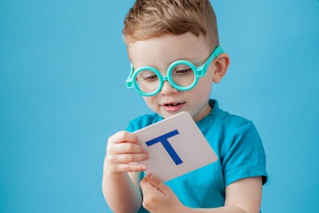 Ładny mały chłopiec z listem na tle. dziecko uczy się liter. alfabet.