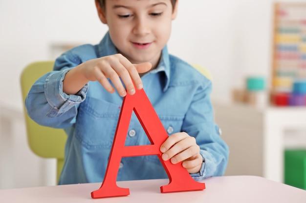 Ładny mały chłopiec z literą a w biurze logopedy
