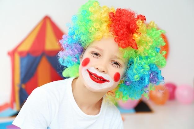 Ładny mały chłopiec z makijażem klauna w tęczowej peruce pomieszczeniu. święto prima aprilis