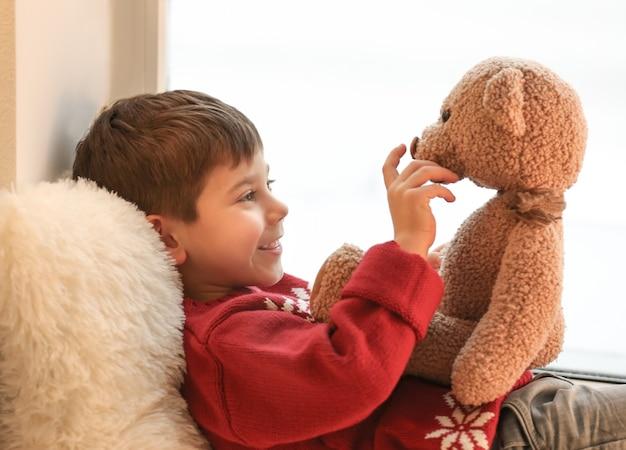 Ładny mały chłopiec z misiem w pobliżu okna w domu