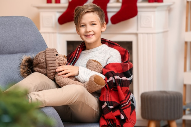 Ładny mały chłopiec z misiem w wigilię bożego narodzenia w domu