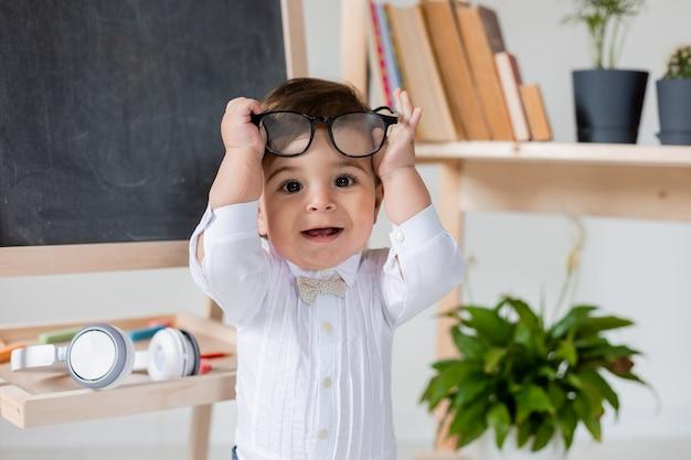 Ładny mały chłopiec z okularami uśmiecha się obok tablicy i książek. edukacja przedszkolna dla dzieci