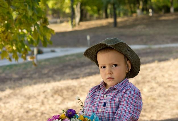 Ładny mały chłopiec z poważnym wyrazem twarzy w kapeluszu przeciwsłonecznym i trzymający bukiet kwiatów na wsi