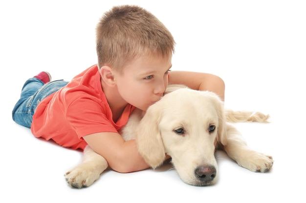 Ładny mały chłopiec z psem na białym tle