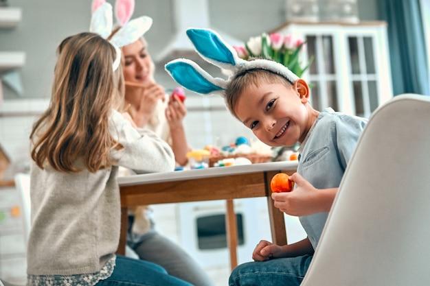 Ładny mały chłopiec z siostrą i matką przygotowują się do obchodów wielkanocy. szczęśliwa rodzina w uszach króliczka spędza razem czas przed wielkanocą podczas malowania jajek.