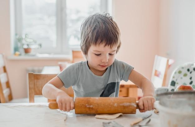 Ładny mały chłopiec za pomocą wałka do ciasta do przygotowania ciasta na ciasteczka w kuchni