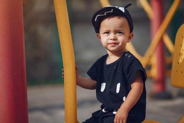 Ładny mały chłopiec zabawy na placu zabaw