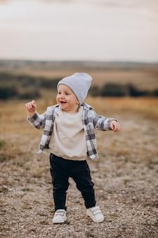 Ładny mały chłopiec zabawy w polu