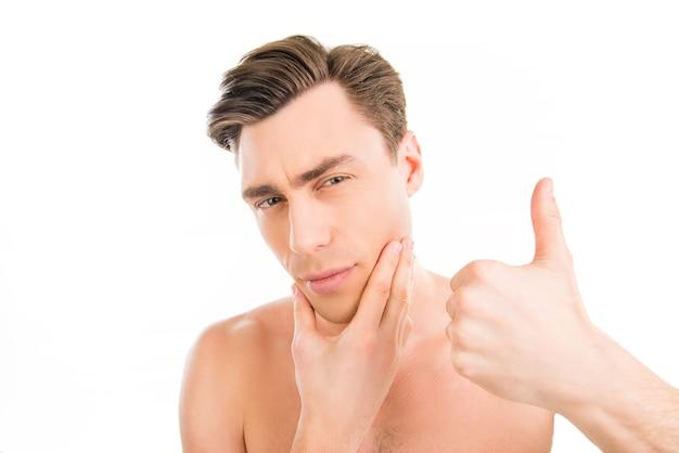 Ładny mężczyzna dotyka jego twarzy po goleniu i gestykulacji
