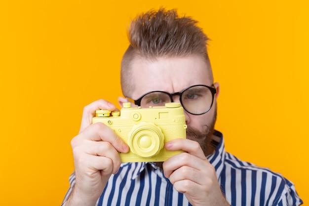 Ładny mężczyzna fotograf fotografuje żółty aparat vintage