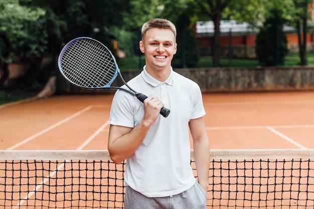 Ładny mężczyzna tenisista. przystojna młoda chłopiec trzyma tenisowego kant i ono uśmiecha się w polo koszula podczas gdy stojący na tenisowym sądzie.
