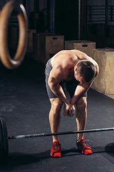 Ładny mężczyzna zmęczony po podnoszeniu ciężarów w siłowni