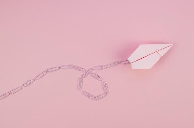 Ładny minimalistyczny papierowy samolot z różowym szlakiem
