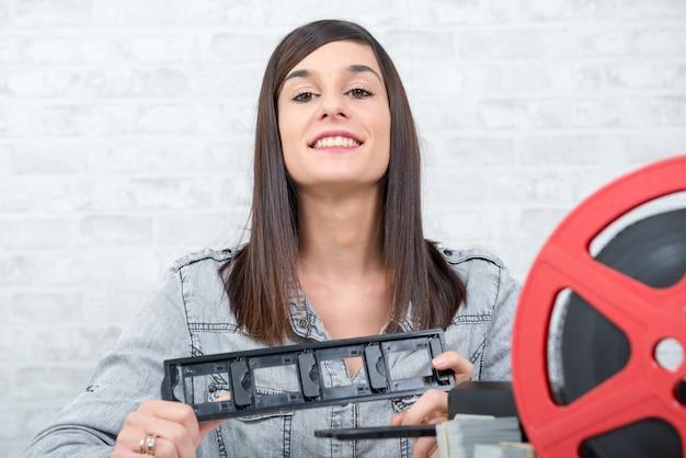 Ładny młoda kobieta technika skanuje obruszenie filmu