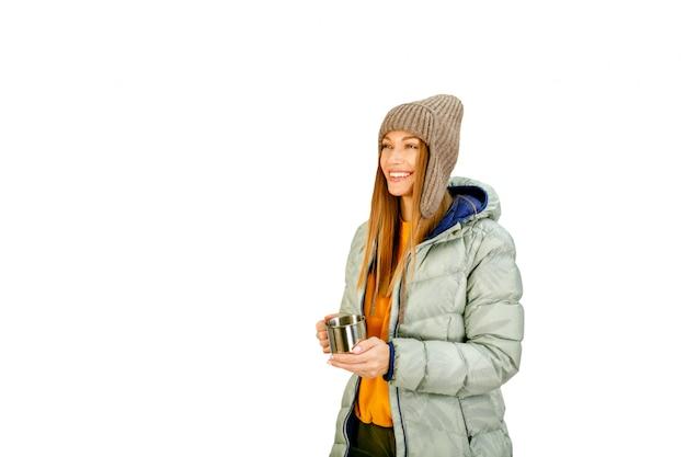 Ładny młoda kobieta turysta w zimie odziewa z gorącym smakowitym napojem odizolowywającym na witce.