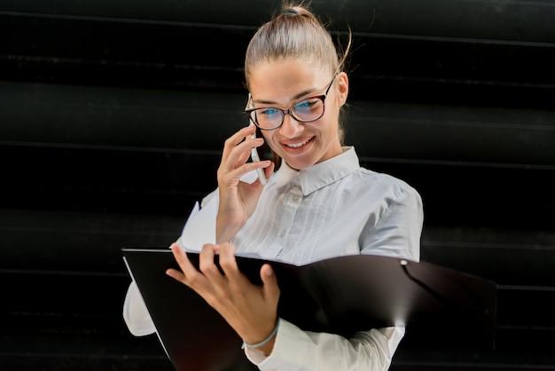 Ładny młody bizneswoman używa telefon komórkowego i trzymać kartotekę