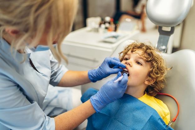 Ładny młody chłopak odwiedza dentystę, po sprawdzeniu zębów przez kobietę dentystę w gabinecie stomatologicznym.