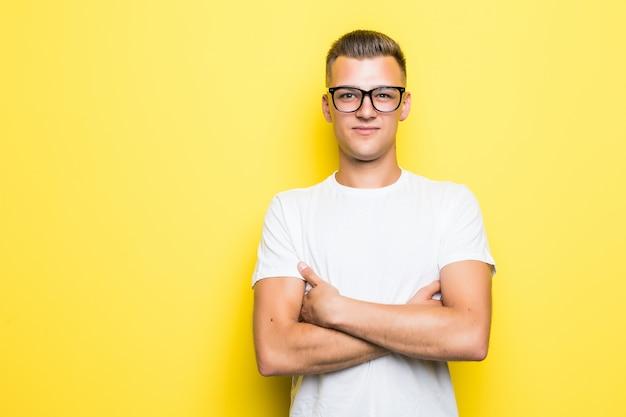 Ładny, młody chłopak trzyma skrzyżowane ręce ubrany w białą koszulkę i przezroczyste okulary