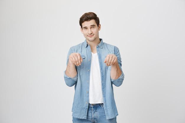 Ładny młody człowiek podnieść ręce naśladując pozę szczeniaka