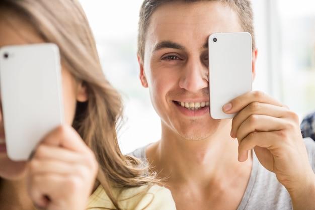 Ładny młody człowiek trzyma jego mądrze telefon.