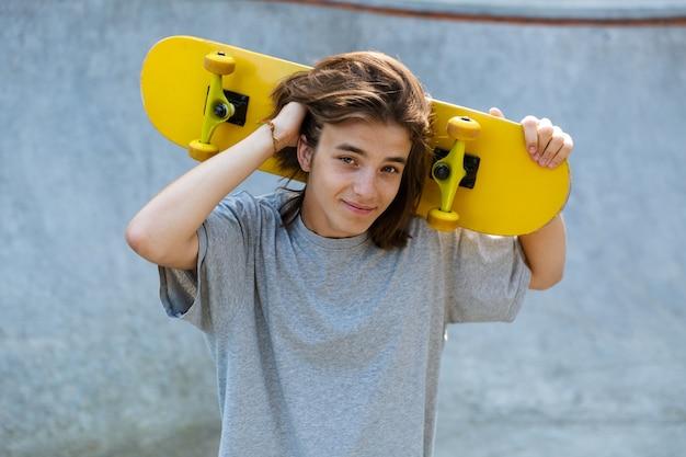 Ładny młody nastolatek spędza czas w skate parku, trzymając deskorolkę