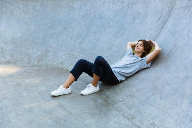 Ładny, młody nastolatek, spędzanie czasu w skate parku, na deskorolce na rampie