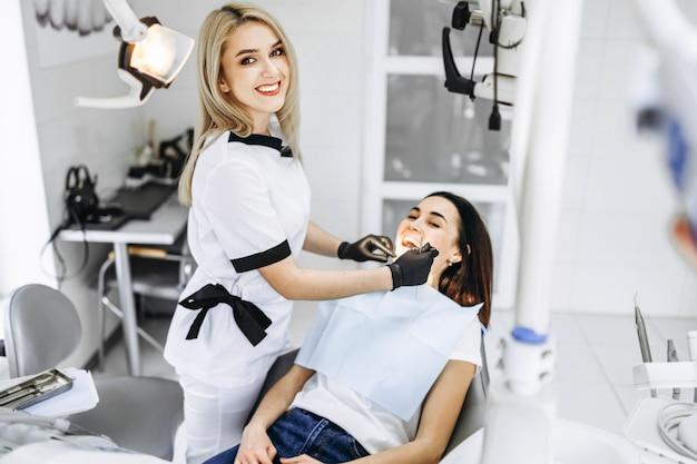 Ładny młody żeński dentysta robi badaniu i leczeniu dla młodego żeńskiego pacjenta w klinice stomatologicznej.