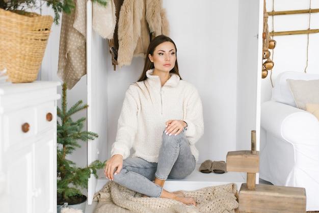 Ładny model dziewczyna siedzi w szafie garderoby w pokoju urządzonym na boże narodzenie i nowy rok