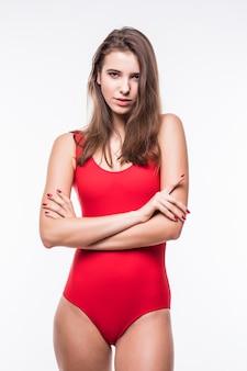 Ładny model dziewczyna w apartamencie pływacki trzyma ręce na jej pasku na białym tle