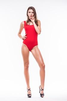 Ładny model dziewczyna w czerwonym apartamencie kąpielowym trzymać ręce pod brodą na białym tle
