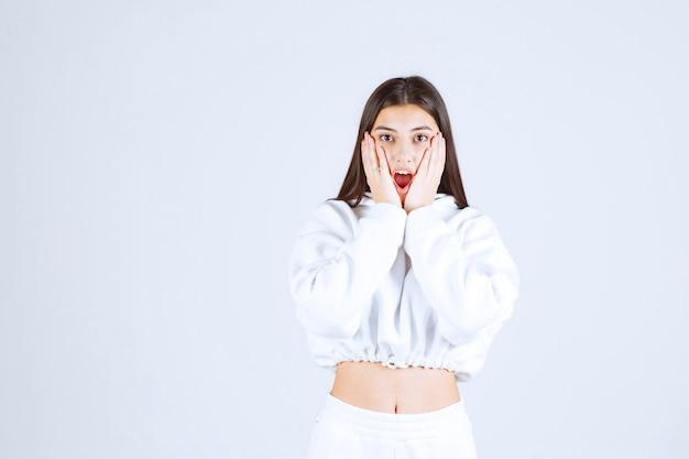Ładny model młoda dziewczyna trzymając się za ręce pod policzkami.