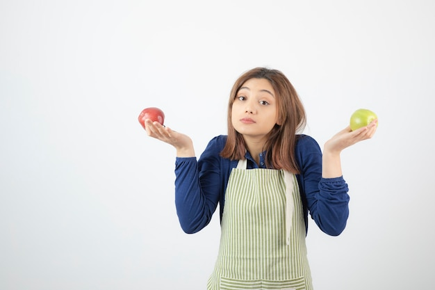 Ładny model młoda kobieta w fartuchu gospodarstwa jabłka.