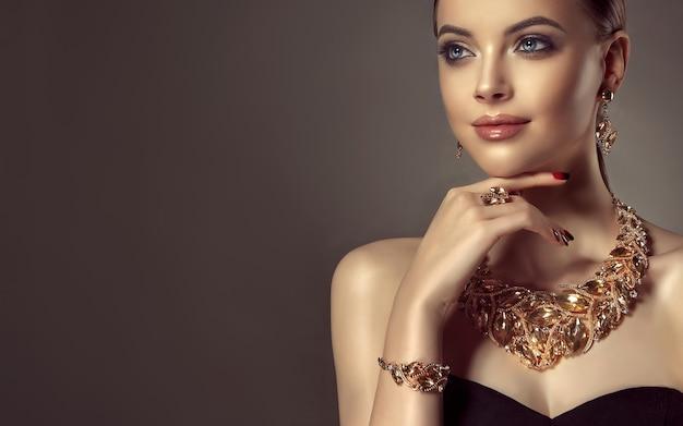 Ładny model o niebieskich oczach z delikatnym uśmiechem na twarzy i wyglądem pełnym romantyzmu wspaniała kobieta ubrana w zestaw biżuterii składający się z naszyjnika i kolczyków