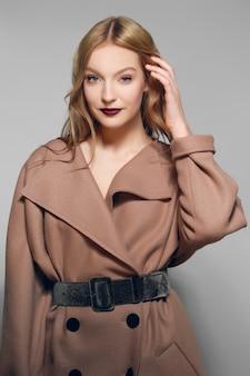 Ładny model w ciepłym wełnianym płaszczu utrwalającym włosy.