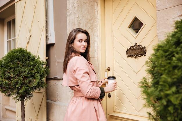 Ładny model w płaszczu z kawą.