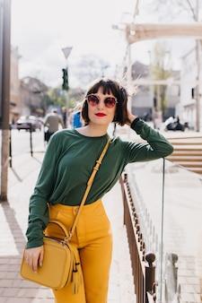 Ładny modelki w żółte spodnie dotykając jej włosów z uśmiechem. zewnątrz portret czarujący dziewczyna brunetka w okularach z elegancką torebką.