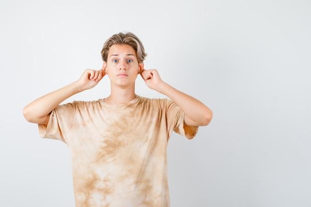 Ładny nastolatek chłopak ściągając płatki uszu w t-shirt i patrząc przestraszony. przedni widok.