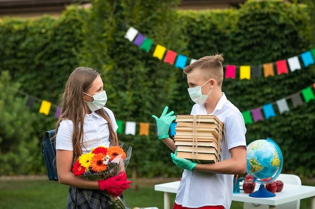 Ładny nastolatek chłopiec i dziewczynka w medycznych maskach i rękawiczkach, trzymając książki i kwiaty i rozmawiając na zewnątrz