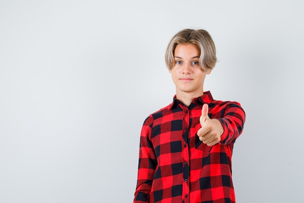 Ładny nastolatek chłopiec pokazując kciuk w kraciastej koszuli i wyglądający na zadowolonego. przedni widok.