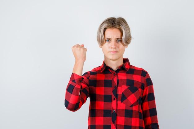 Ładny nastolatek chłopiec pokazując zaciśniętą pięść w kraciastej koszuli i patrząc dumny, widok z przodu.