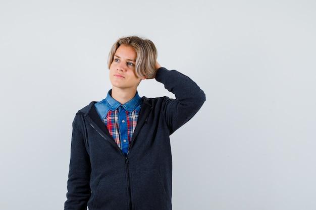 Ładny nastolatek chłopiec trzymając rękę za głowę, odwracając wzrok w koszulę, bluzę z kapturem i patrząc zamyślony. przedni widok.