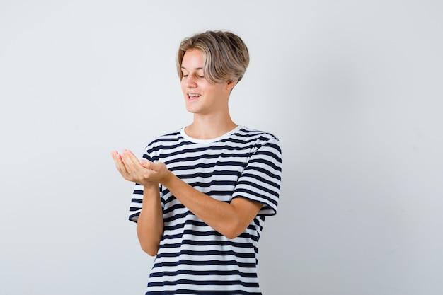 Ładny nastoletni chłopak patrzący na jego złożone dłonie w pasiastym t-shircie i patrzący wesoło, widok z przodu.