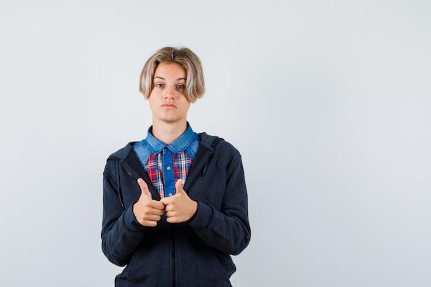 Ładny nastoletni chłopak w koszuli, bluzie z kapturem, pokazując podwójne kciuki w górę i patrząc zadowolony, widok z przodu.